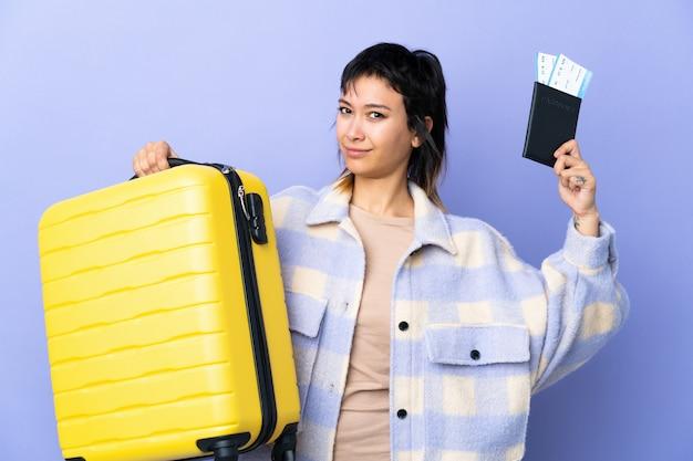 Junge uruguayische frau über isolierte lila wand unglücklich im urlaub mit koffer und pass
