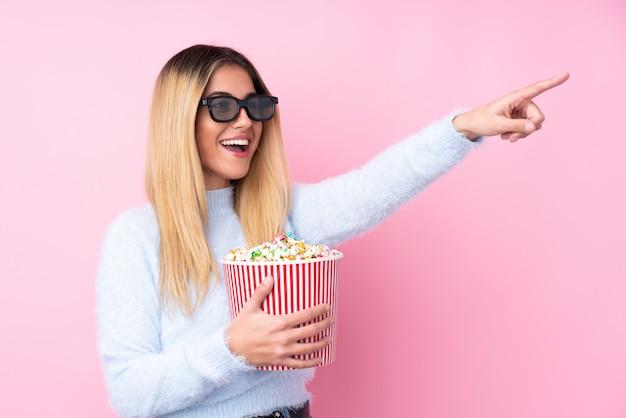 Junge uruguayische frau über isolierte rosa wand mit 3d-brille und hält einen großen eimer popcorn beim wegweisen