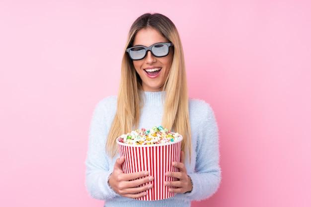 Junge uruguayische frau über isolierte rosa wand mit 3d-brille und hält einen großen eimer popcorn