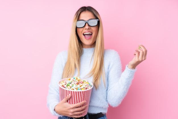 Junge uruguayische frau über isolierte wand rosa wand mit 3d-brille und hält einen großen eimer popcorn