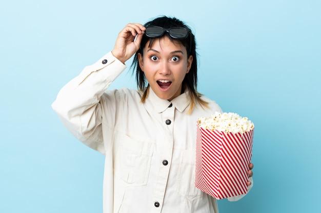Junge uruguayische frau über isoliertem blau überrascht mit 3d-brille und hält einen großen eimer popcorn