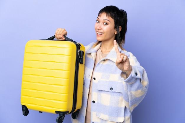 Junge uruguayische frau über isoliertem purpur im urlaub mit reisekoffer und zählen eines