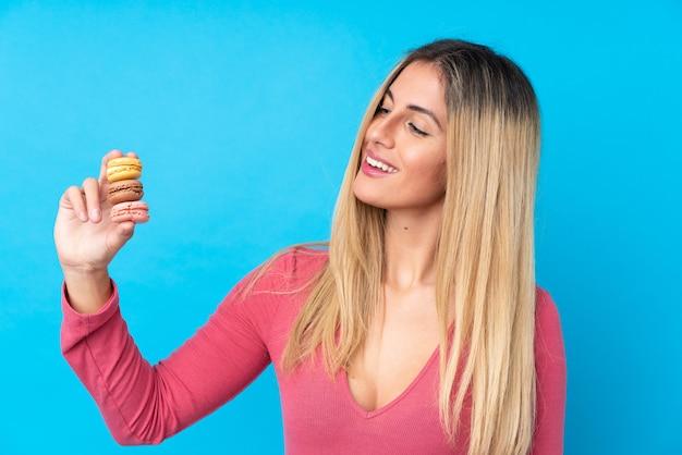Junge uruguayische frau über isolierter blauer wand, die bunte französische macarons und glücklich hält