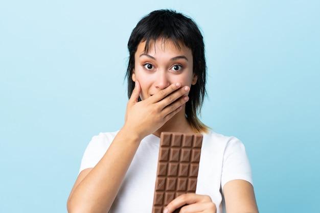 Junge uruguayische frau über isolierter blauer wand, die eine schokoladentafel nimmt und überrascht