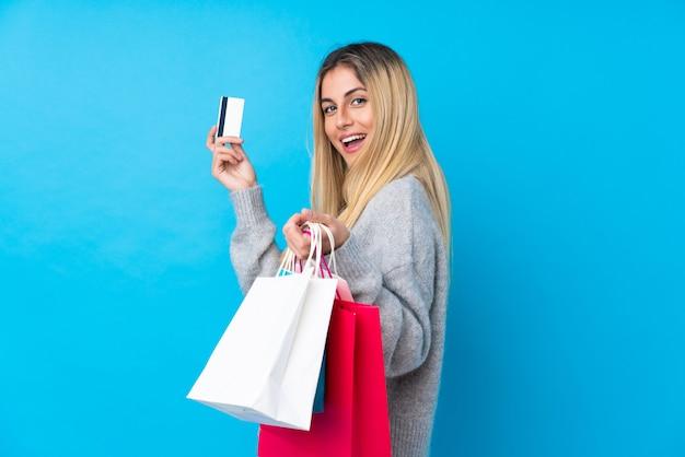 Junge uruguayische frau über isolierter blauer wand, die einkaufstaschen und eine kreditkarte hält