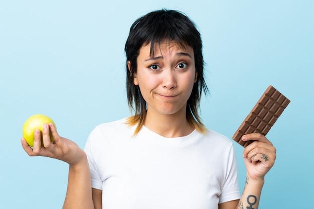 Junge uruguayische frau über isolierter blauer wand, die zweifel hat, während sie eine schokoladentafel in einer hand und einen apfel in der anderen nimmt