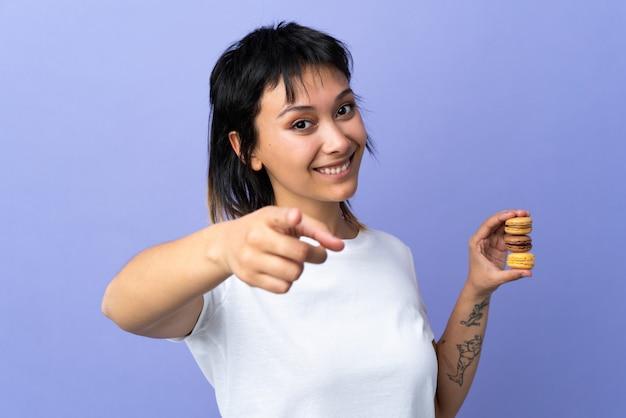 Junge uruguayische frau über isolierter lila wand, die bunte französische macarons hält und finger auf sie zeigt