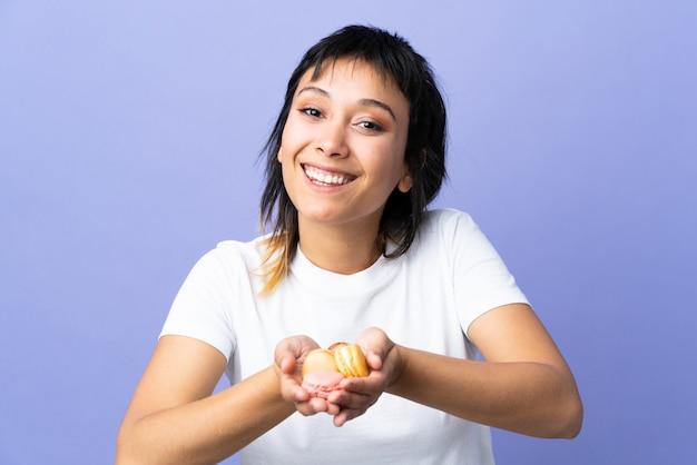 Junge uruguayische frau über isolierter lila wand, die bunte französische macarons hält