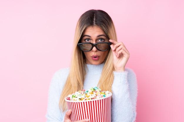 Junge uruguayische frau über isolierter wand rosa wand überrascht mit 3d-brille und hält einen großen eimer popcorn