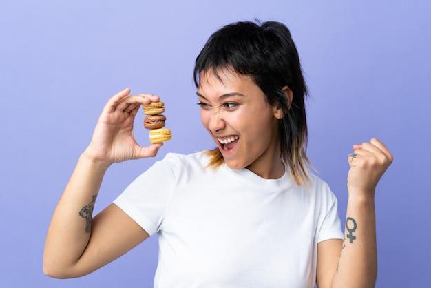 Junge uruguayische frau über lila wand, die bunte französische macarons hält und einen sieg feiert