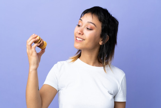 Junge uruguayische frau über lila wand, die bunte französische macarons und glücklich hält