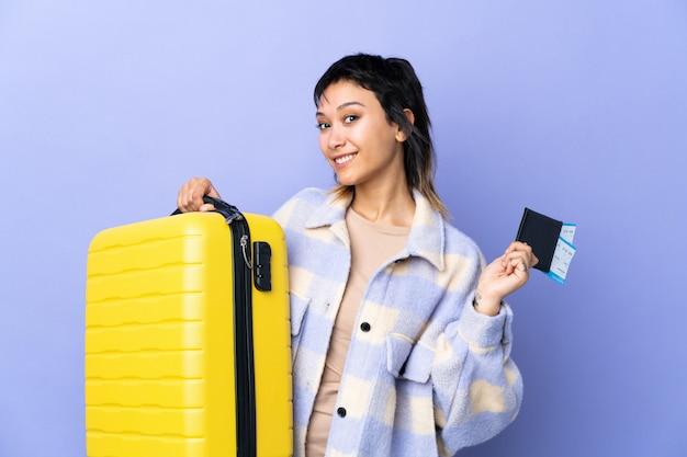 Junge uruguayische frau über lila wand im urlaub mit koffer und pass