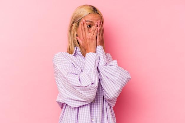 Junge venezolanische frau, die auf rosa hintergrund lokalisiert wird, blinzelt durch erschrockene und nervöse finger.