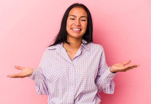 Junge venezolanische frau, die auf rosafarbenem hintergrund isoliert ist, macht mit armen eine waage, fühlt sich glücklich und selbstbewusst.