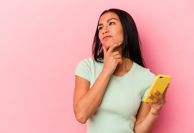 Junge venezolanische frau, die ein mobiltelefon isoliert auf rosafarbenem hintergrund hält und seitlich mit zweifelhaftem und skeptischem ausdruck schaut.