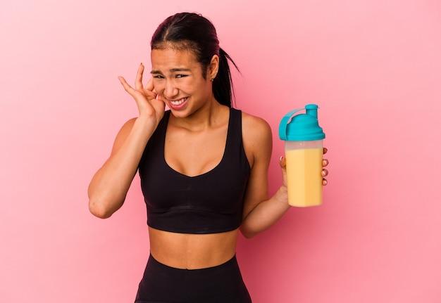 Junge venezolanische frau, die einen proteinshake trinkt, isoliert auf rosa hintergrund