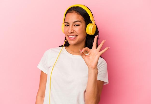 Junge venezolanische frau, die musik einzeln auf rosafarbenem hintergrund hört, fröhlich und selbstbewusst, die eine ok geste zeigt.