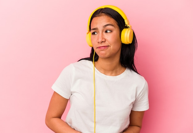 Junge venezolanische frau, die musik einzeln auf rosafarbenem hintergrund hört, verwirrt, fühlt sich zweifelhaft und unsicher.