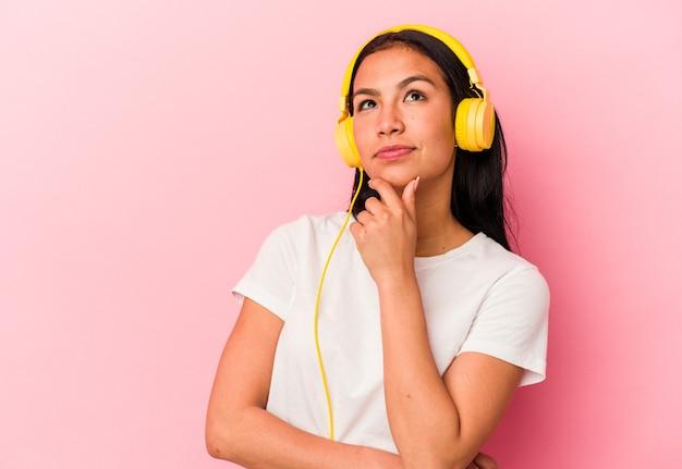 Junge venezolanische frau, die musik hört, einzeln auf rosafarbener wand, die seitlich mit zweifelhaftem und skeptischem ausdruck schaut.