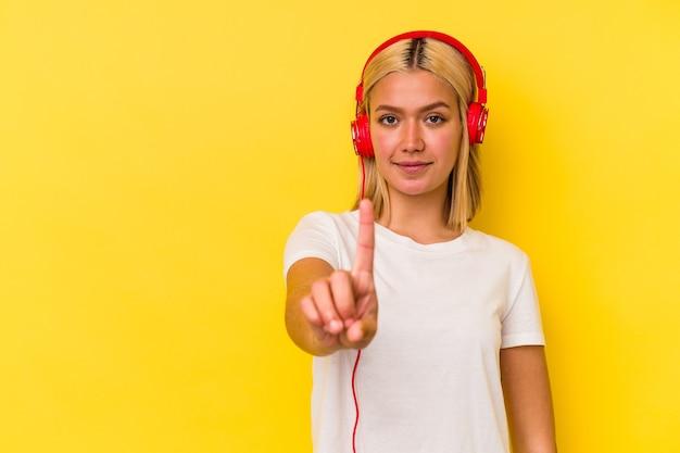 Junge venezolanische frau, die musik lokalisiert auf gelber wand hört, die nummer eins mit finger zeigt.