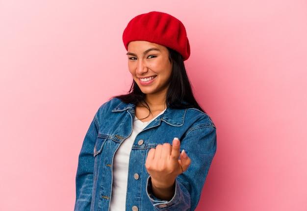 Junge venezolanische frau einzeln auf rosafarbenem hintergrund, die mit dem finger auf sie zeigt, als ob sie einladen würde, näher zu kommen.