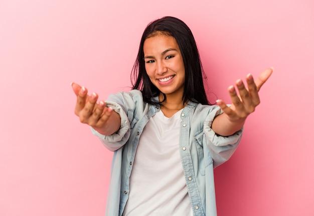 Junge venezolanische frau isoliert auf rosa hintergrund mit einem willkommenen ausdruck.