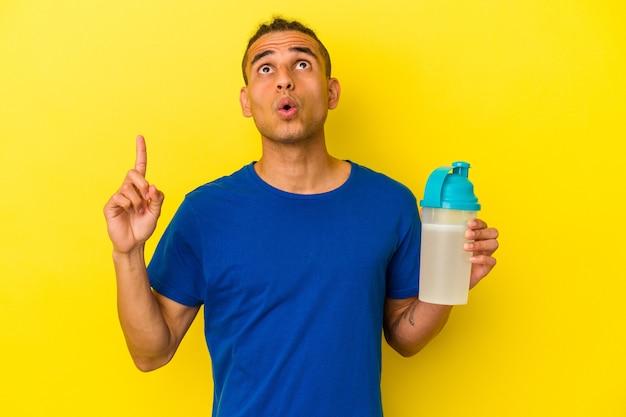 Junge venezolanische mann, der einen proteinshake trinkt, der auf gelbem hintergrund isoliert ist und mit geöffnetem mund nach oben zeigt.