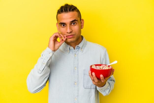Junge venezolanische mann hält eine müslischale isoliert auf gelbem hintergrund mit den fingern auf den lippen