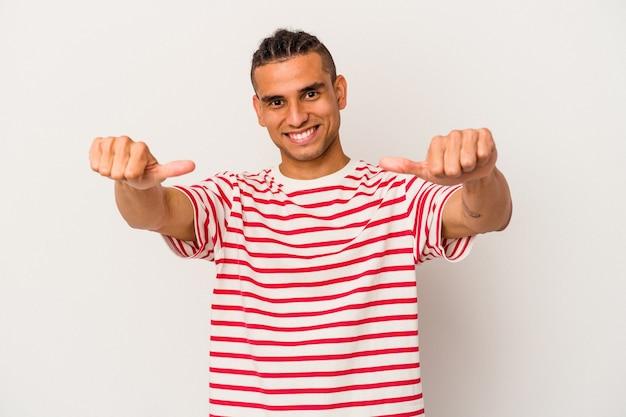 Junge venezolanische mann isoliert auf weißem hintergrund hob beide daumen hoch, lächelnd und selbstbewusst.