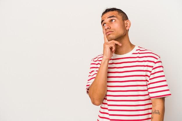 Junge venezolanische mann isoliert auf weißem hintergrund mit zweifelhaftem und skeptischem ausdruck seitlich suchen.