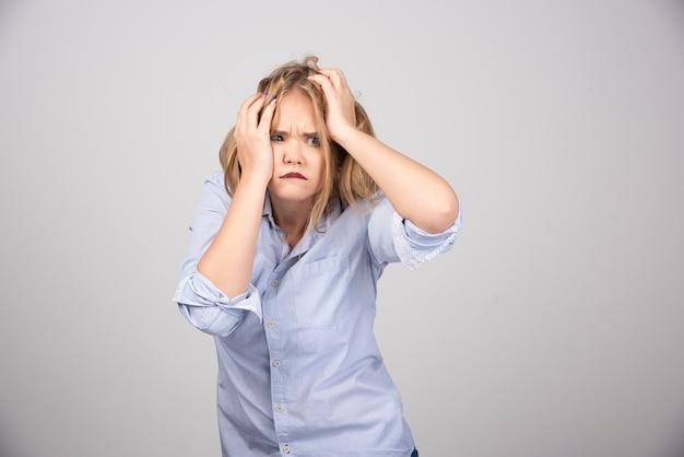 Junge verängstigte blonde frau mit geöffnetem mund, der die hände auf dem kopf hält.