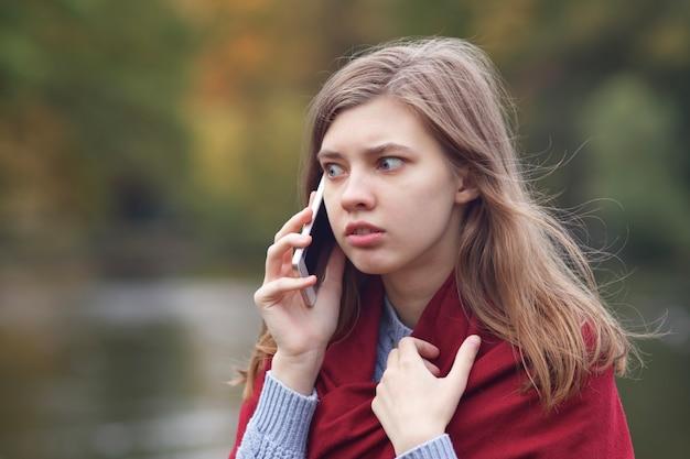 Junge verängstigte, verängstigte, wütende frau, die auf ihrem handy spricht und einen negativen anruf hat