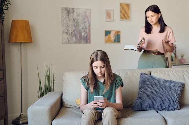 Junge verärgerte brünette mutter mit heft ihrer tochter im teenageralter, die auf der couch hinter dem mädchen steht, das im handy sms schreibt