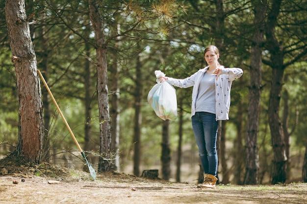Junge verärgerte frau, die müll säubert, müllsäcke hält und daumen nach unten im park zeigt. problem der umweltverschmutzung