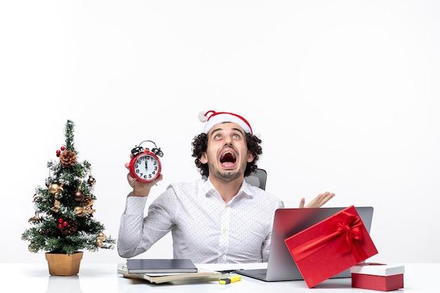 Junge verärgerte geschäftsperson mit weihnachtsmannhut und halten der uhr und des sitzens im büro auf dunklem hintergrund