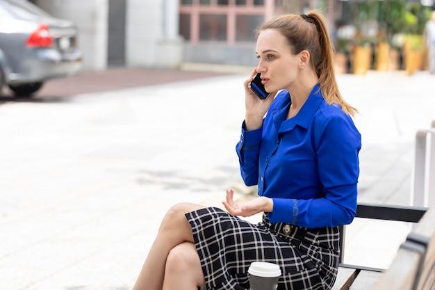 Junge verärgerte kaukasische führungskraft, die am telefon streitet, während sie auf einer bank auf der straße ruht