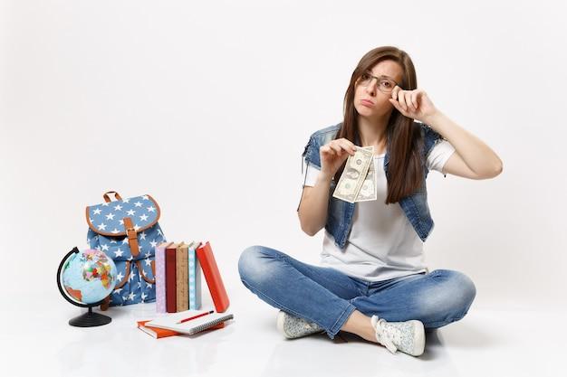 Junge verärgerte studentin, die weinende dollarnoten hält und sich durch geldmangel gestresst fühlt, sitzt in der nähe des globus, rucksackschulbücher isoliert