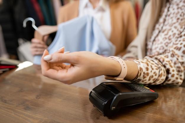Junge verbraucherin mit smartwatch am handgelenk, die ihren arm über pos terminal auf theke hält, während sie für kleidung in der boutique bezahlt