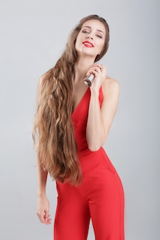 Junge verführerische frau im roten kleid, das parfüm auf ihrem hals aufträgt. freude am duft