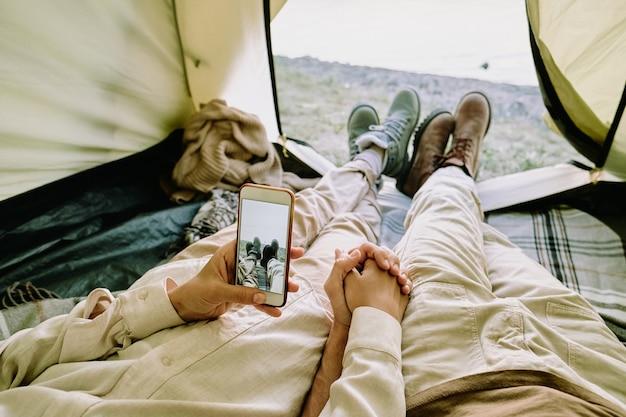 Junge verliebte frau mit smartphone, die ihren ehemann an der hand hält und foto von ihnen macht, die nebeneinander im zelt liegen
