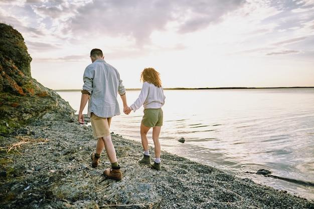 Junge verliebte wanderer in freizeitkleidung, die durch hände halten, während sie sich entlang der küste durch wasser mit bewölktem himmel über bewegen und romantische zeit genießen