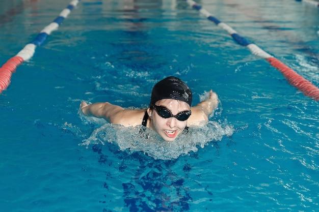 Junge verrückte frau in schutzbrille und mütze schwimmen schmetterlingsstil im blauen wasser indoor-rennpool.
