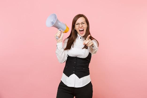 Junge verrückte geschäftsfrau in schwarzem anzug und brille schreien mit megaphon, der den zeigefinger einzeln auf rosafarbenem hintergrund zeigt. chefin. erfolg karriere reichtum. kopieren sie platz für werbung.