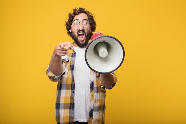 Junge verrückte verrückte manndummkopfhaltung mit einem megaphon. ankündigung co