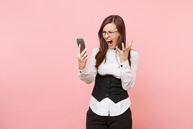 Junge verrückte wütende geschäftsfrau im schwarzen anzug, brille schreiend, die das handy hält, das die hände einzeln auf rosafarbenem hintergrund ausbreitet. chefin. erfolg karriere reichtum. kopieren sie platz für werbung.