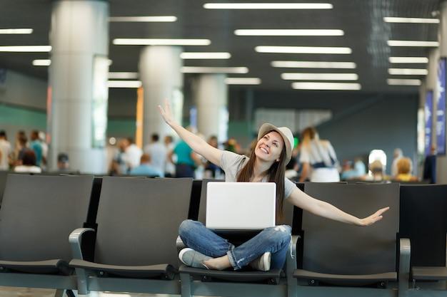 Junge verträumte reisende touristenfrau mit laptop sitzt mit gekreuzten beinen und spreizt die hände wie im flug und wartet in der lobbyhalle am flughafen?