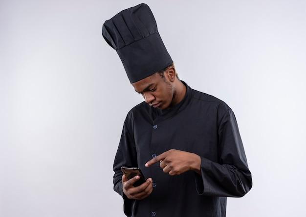 Junge verwirrte afroamerikanische köchin in der kochuniform betrachtet und zeigt auf telefon lokalisiert auf weißer wand