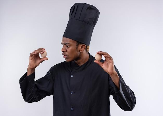 Junge verwirrte afroamerikanische köchin in der kochuniform hält eier auf beiden händen lokalisiert auf weißer wand