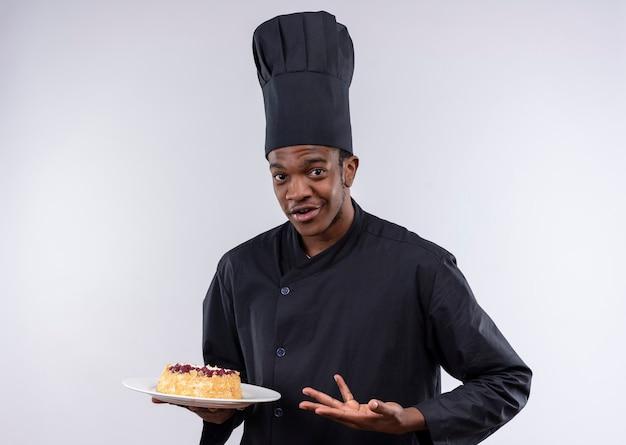 Junge verwirrte afroamerikanische köchin in der kochuniform hält kuchen auf teller und zeigt mit hand lokalisiert auf weißer wand