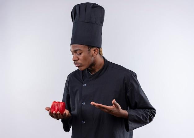 Junge verwirrte afroamerikanische köchin in der kochuniform hält roten pfeffer und punkte mit der hand lokalisiert auf weißer wand